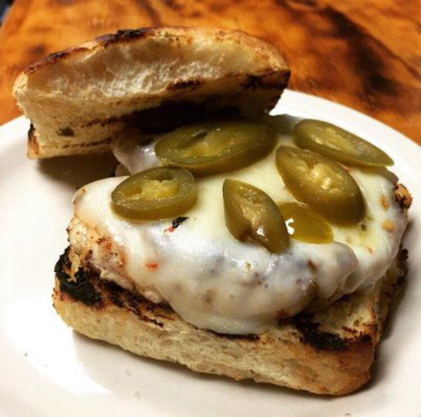 Chicken breast sandwich topped with pepper Jack cheese and jalapenos